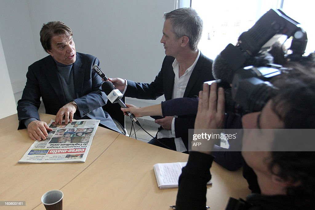 The new owner of the Nice Matin press group Bernard Tapie (L) talks to journalists after meeting the group's employees on March 13, 2013 at the group's printing house in Bastia, Corsica.