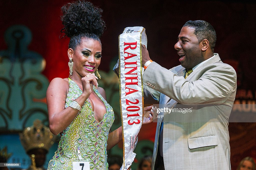 The new Queen of Sao Paulo's carnival, Ariellen da Silva Domiciano (L) receives the sash during the competition for new King, Queen and Princess of the Carnival parade in Sao Paulo, Brazil, late on January 17, 2013. Sao Paulo's carnival is scheduled for February 8 and 9.
