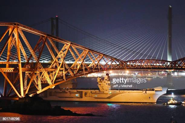 The new Royal Navy aircraft carrier HMS Queen Elizabeth is pulled by tug boats underneath the Forth Rail Bridge as departs for sea trials in the...