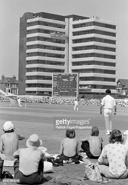 The new scoreboard is dwarfed by the modern multistorey office block on the far side of the ground as some young spectators get a close view of the...