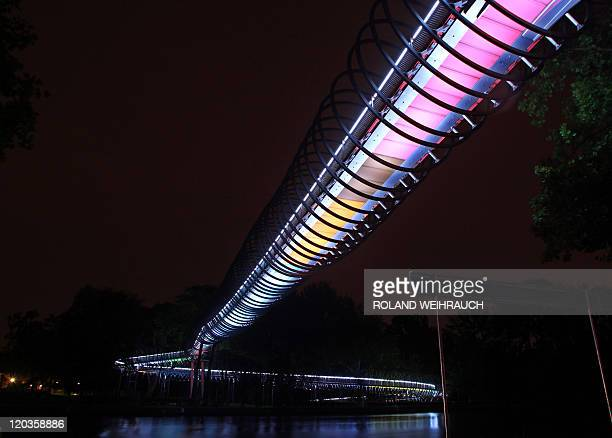 The new 'Slinky Springs to Fame' bridge is illuminated at night in the western German city of Oberhausen on August 4 2011 The 350meterlong bridge was...