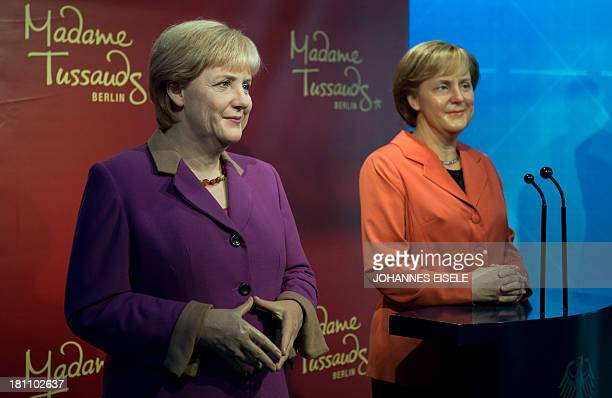 The new wax likeness of German Chancellor Angela Merkel features her signature diamond shape pose and is pictured next to a 2005 likeness during an...