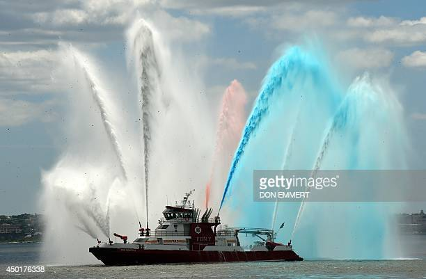 The New York City fireboat sprays colored water into the New York Harbor June 6 2014 in New York Thousands gathered on the Liberty Island to...