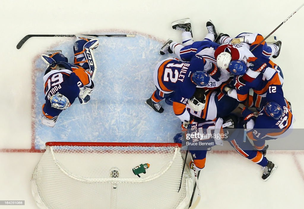 The New York Islanders and the Montreal Canadiens pile up after Gabriel Dumont #37 ran into <a gi-track='captionPersonalityLinkClicked' href=/galleries/search?phrase=Evgeni+Nabokov&family=editorial&specificpeople=171380 ng-click='$event.stopPropagation()'>Evgeni Nabokov</a> #20 at the Nassau Veterans Memorial Coliseum on March 21, 2013 in Uniondale, New York. The Canadiens defeated the Islanders 5-2.