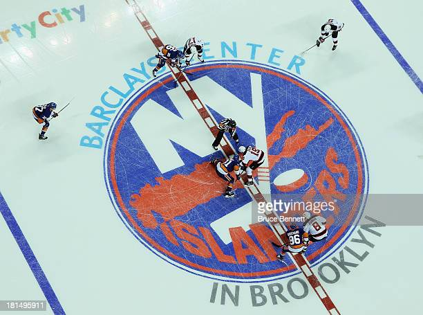 The New York Islanders and the New Jersey Devils drop the opening puck during a preseason game at the Barclays Center on September 21 2013 in...