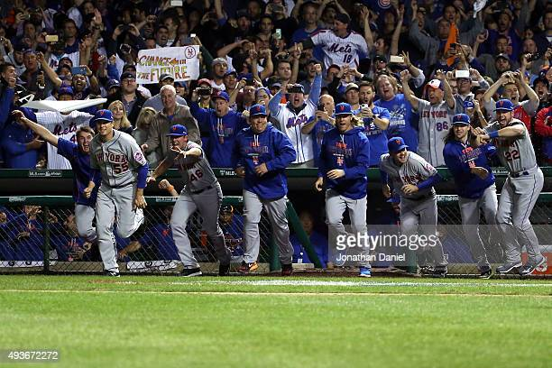 The New York Mets dugout rushes the field to celebrate with his team after defeating the Chicago Cubs in game four of the 2015 MLB National League...
