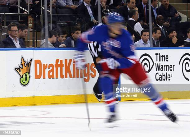 The New York Rangers and St Louis Blues skate in front of a dasher board advertising the betting website DraftKings at Madison Square Garden on...