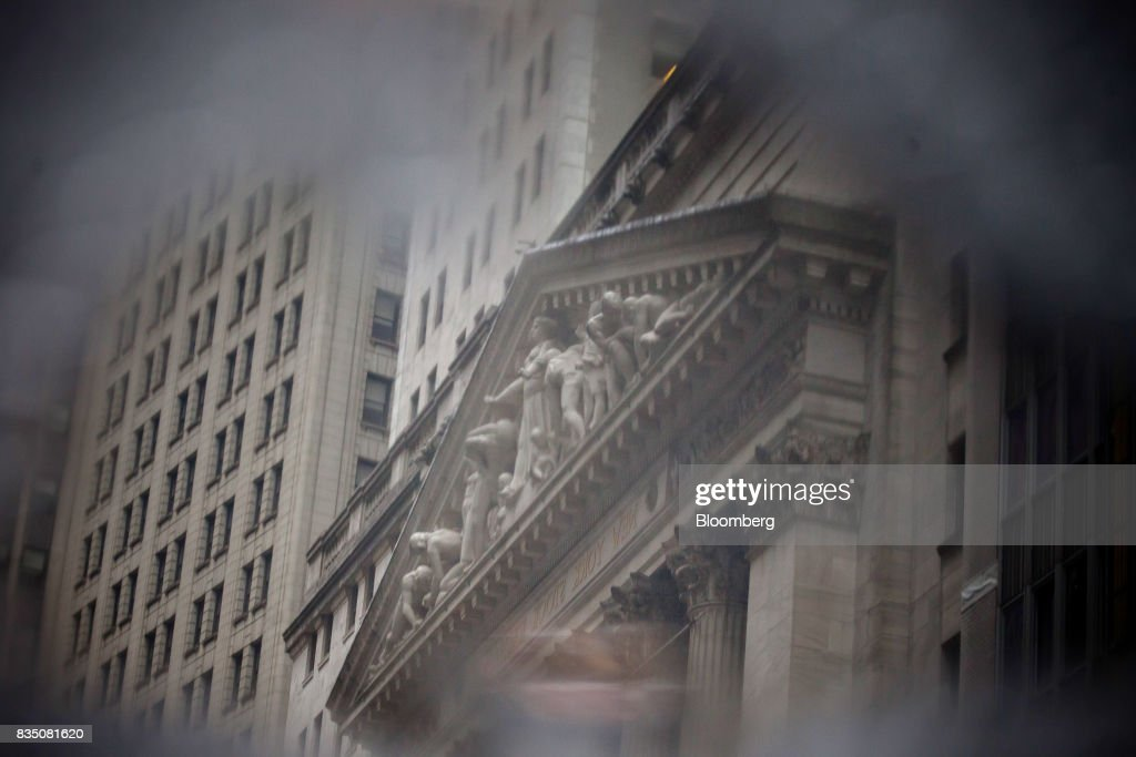 The New York Stock Exchange (NYSE) is reflected in a puddle in New York, U.S., on Friday, Aug. 18, 2017. Stocks were mixed and the S&P 500 Index turned higher as investors digested the political upheaval in the U.S. and the latest terrorist attack in Europe. Photographer: Michael Nagle/Bloomberg via Getty Images