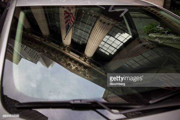 The New York Stock Exchange is reflected in the windshield of a General Motors Co Maven carsharing service vehicle in New York US on Monday May 15...