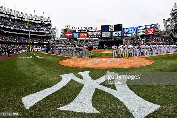 The New York Yankees and the Detroit Tigers look on as West Point Cadets unfurl the American Flag during the opening ceremonies on Opening Day at...