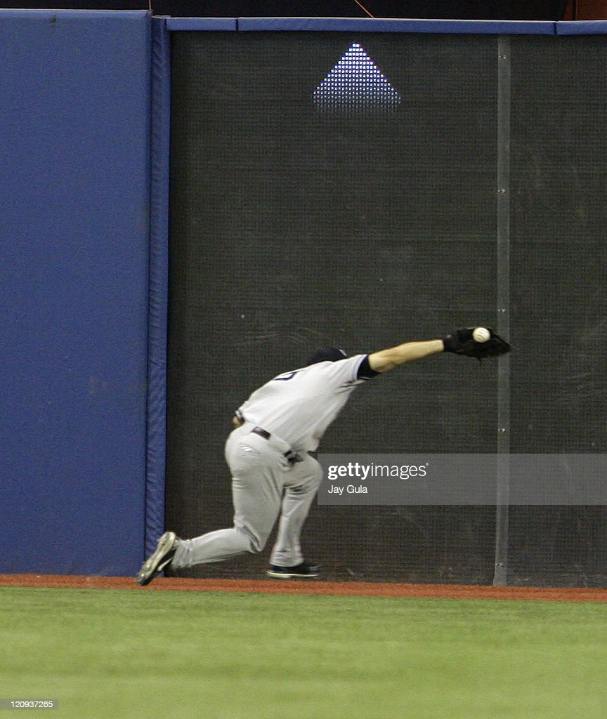 The New York Yankees' CF Bubba Crosby made a valiant effort to catch this ball off the bat of Toronto's Vernon Wells but it glanced off his glove...
