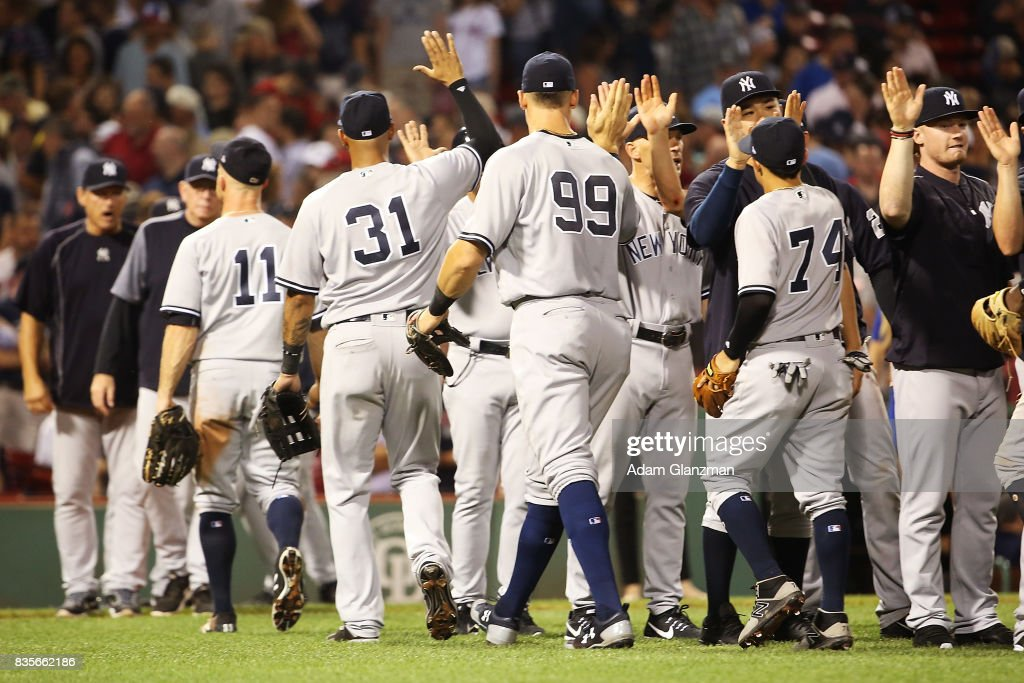 The New York Yankees high five each other after the victory over the Boston Red Sox at Fenway Park on August 19, 2017 in Boston, Massachusetts.
