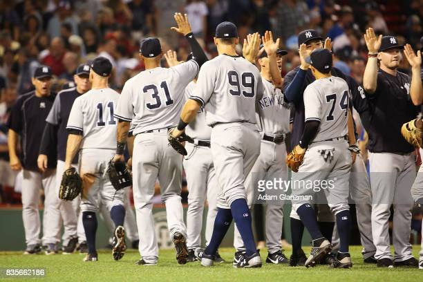 The New York Yankees high five each other after the victory over the Boston Red Sox at Fenway Park on August 19 2017 in Boston Massachusetts