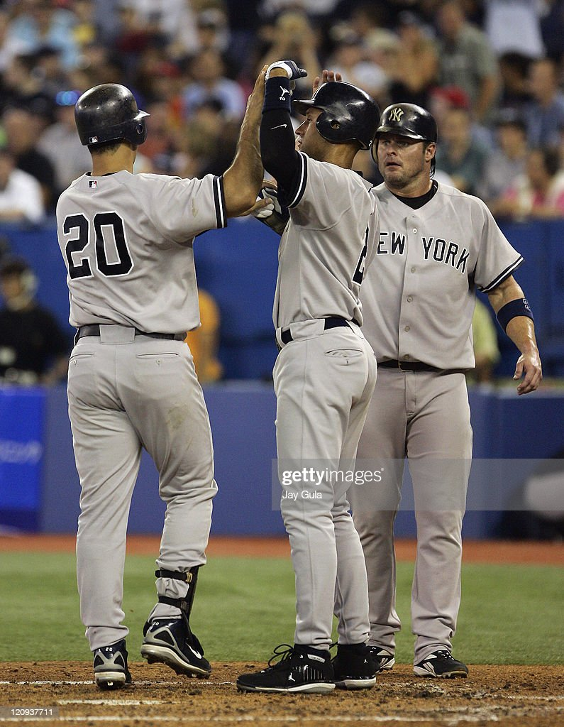 The New York Yankees' Jason Giambi and Derek Jeter congtaulate Jorge Posada after his 3 run HR in the 3rd inning against the Toronto Blue Jays at...