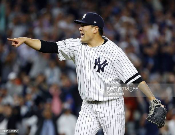 The New York Yankees' Masahiro Tanaka points toward home plate after striking out the Houston Astros' Marwin Gonzalez to end the seventh inning in...