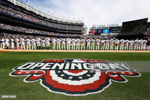 The New York Yankees stand for the National Anthem before the game against the Tampa Bay Rays during the New York Yankees home Opening game at Yankee...