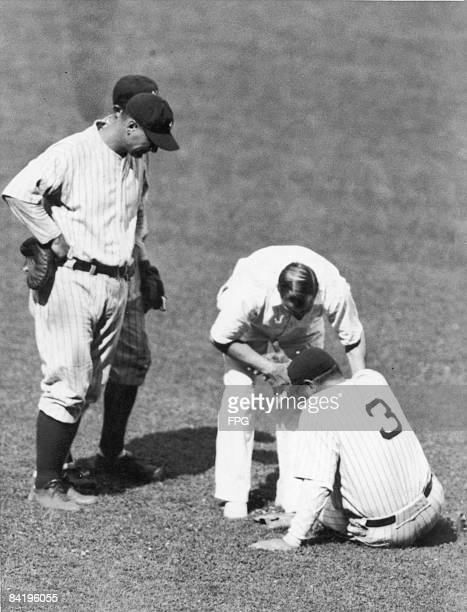 The New York Yankees team doctor examines injured American baseball player Babe Ruth as teammate Lou Gehrig watches during a game 1920s