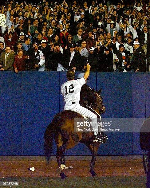 The New York Yankees' Wade Boggs waves to crowd from police horse after the Yankees won the World Series