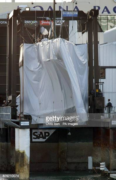 The New Zealand America's Cup yacht is lifted out of Auckland's Viaduct Harbour shrouded by a huge tarpaulin skirt to hide its keel and rudder from...