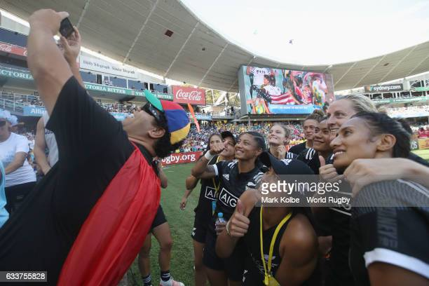 The New Zealand players pose for a selfie with a person in the crowd after winning the womens bronze cup match between New Zealand and Australia in...