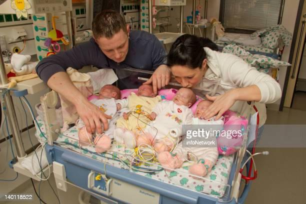 The newborn quadruplets Laura Sophie Jasmin und Kim Mehnert lie on a bed as their parents Janett Mehnert and Marcus Mehnert stand behind at Leipzig...
