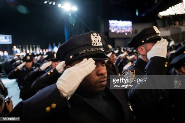 The newest members of the New York City Police Department salute toward their families during their police academy graduation ceremony at the Theater...