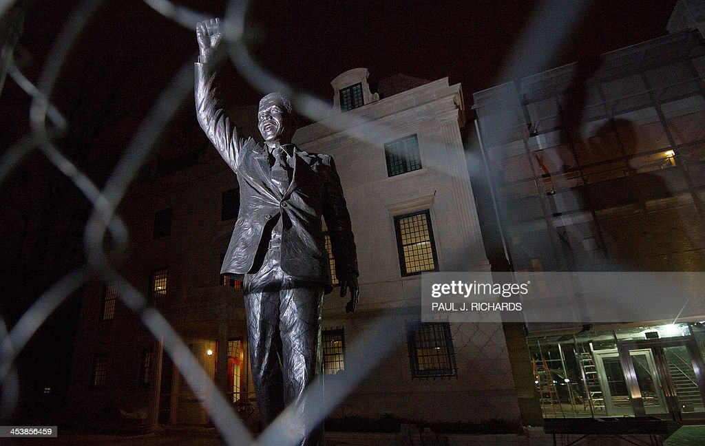 The newly installed statue of South African leader Nelson Mandela seen in front of the South African Embassy, behind a construction style chainlink fence as remodeling is ongoing, December 5, 2013, in Washington, DC. AFP Photo/Paul J. Richards