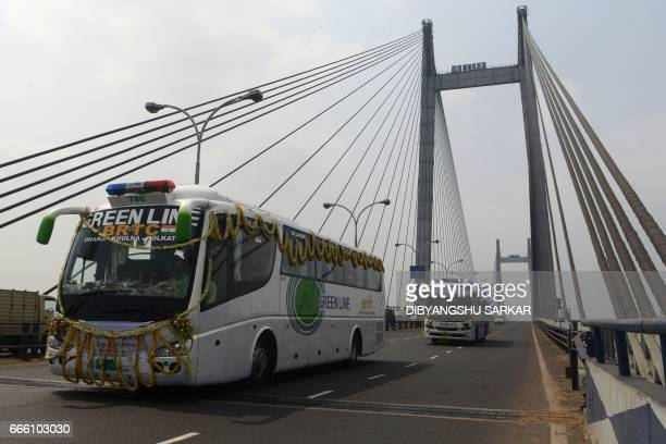 The newly launched KolkataKhulna bus trip drives over the Vibyasagar Setu on the River Ganges after it was flagged off in Kolkata on April 8 2017 As...