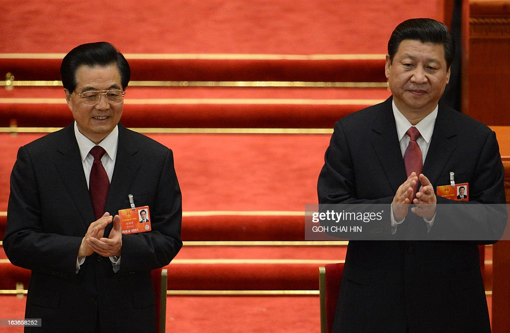 The newly-elected Chinese President Xi Jinping (R) stands with former President Hu Jintao (R) after the election of the new president of China during the 12th National People's Congress (NPC) in the Great Hall of the People in Beijing on March 14, 2013. Chinese Communist Party leader Xi Jinping was named president of the world's most populous country after a vote at its parliamentary meeting in Beijing. AFP PHOTO /GOH CHAI HIN