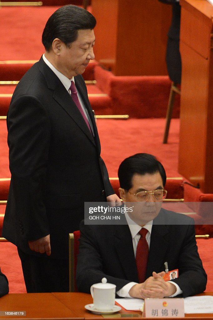 The newly-elected Chinese President Xi Jinping (L) walks past former Chinese president Hu Jintao after Xi delivers his maiden speech at the closing session of the National People's Congress (NPC) at the Great Hall of the People in Beijing on March 17, 2013. Xi said he would fight for a 'great renaissance of the Chinese nation', in his first speech as head of state of the world's most populous country. AFP PHOTO/GOH CHAI HIN
