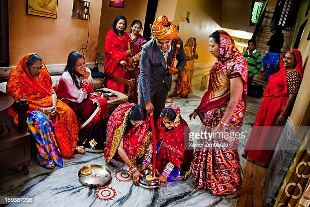 The newlywed couple performing a ritual as the groom's family helps them on January 4 2012 at Sancheti House in Pali Marwar Rajasthan India