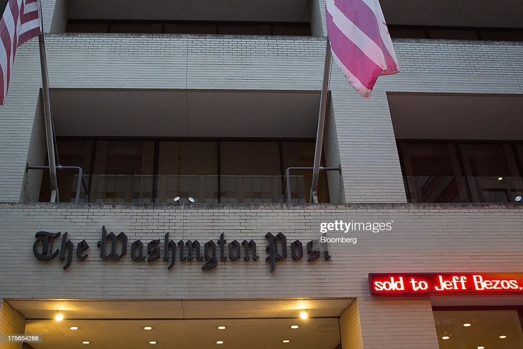 The news that that the Washington Post is to be sold to billionaire Jeff Bezos is displayed on an electronic ticker board outside the Washington Post Co. headquarters in Washington, D.C., U.S., on Monday, Aug. 5, 2013. Amazon.com Inc. Chief Executive Officer Jeff Bezos agreed to buy the Washington Post for $250 million, betting that he can apply his success in e-commerce to the struggling newspaper industry. Photographer: Andrew Harrer/Bloomberg via Getty Images