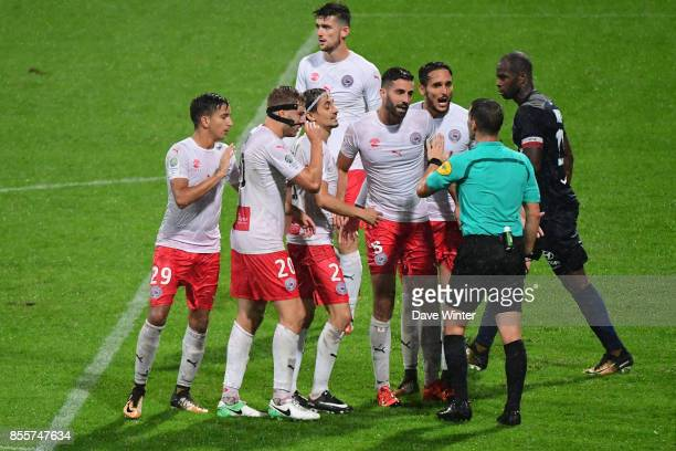 The Nimes players surround referee Jeremy Stinat after their last minute equaliser is disallowed for offside during the Ligue 2 match between Paris...