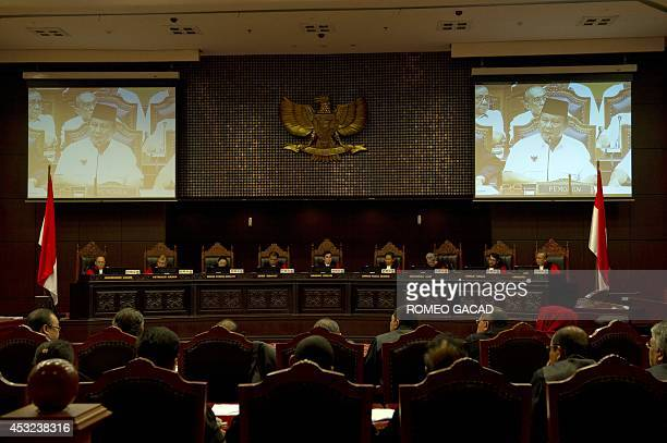 The ninejudge panel of Indonesia's Constitutional Court listen to the address of losing presidential candidate Prabowo Subianto seen on the screens...