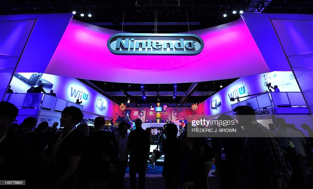 The Nintendo section attracts a crowd on the opening day of the E3 videogame conference in Los Angeles on June 5, 2012 in California, where Nintendo fired its riposte in the battle for living room entertainment by boosting its game offerings for its new Wii U console featuring a tablet-style controller. The Japanese electronic games giant boasted that Wii U would start a 'revolutionary' trend in 'asymmetrical play' that lets players using GamePad tablets act as wily adversaries in multi-person matches. AFP PHOTO/Frederic J. BROWN