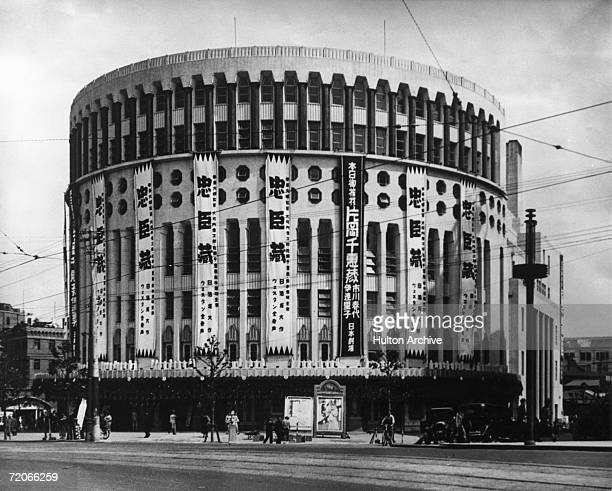 A round cinema building in Tokyo with advertising banners hanging down the outside circa 1960