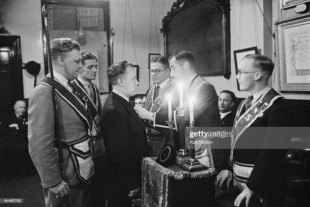 The Noble Grand of the 'Pride of Clapham' lodge of the Manchester Unity of Odd Fellows pins a membership badge on a newlyelected member August 1939...