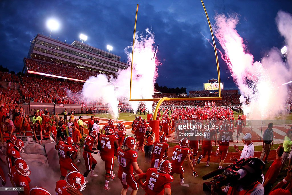 The North Carolina State Wolfpack run onto the field during introductions before their game against the Clemson Tigers at Carter-Finley Stadium on September 19, 2013 in Raleigh, North Carolina.