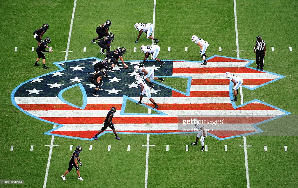 The North Carolina Tar Heels and the East Carolina Pirates line up on the special Military Appreciation Day logo at midfield during play at Kenan Stadium on September 28, 2013 in Chapel Hill, North Carolina.