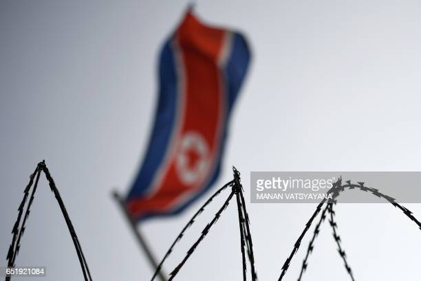The North Korean flag is seen flying in backdrop of barbed wire at the North Korean embassy in Kuala Lumpur on March 11 2017 Malaysia's police chief...