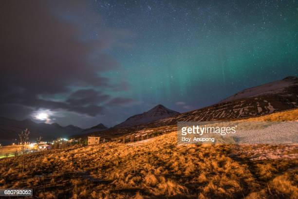 The Northern Lights over the mountains in East fjord of Iceland during the full moon night.