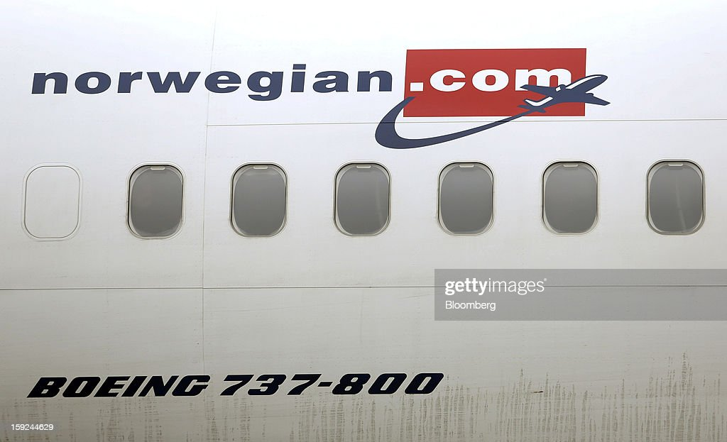 The Norwegian Air Shuttle AS company logo is seen displayed on the side of a Boeing 737-800 aircraft at Gatwick airport in Crawley, U.K., on Thursday, Jan. 10, 2013. Gatwick, acquired by Global Infrastructure Partners Ltd. in 2009 after regulators sought a breakup of BAA Ltd., owner of the larger Heathrow hub, is 30 miles (48 kilometers) south of London and serves about 200 destinations, more than any other U.K. airport, according to flight schedule data provider OAG. Photographer: Chris Ratcliffe/Bloomberg via Getty Images