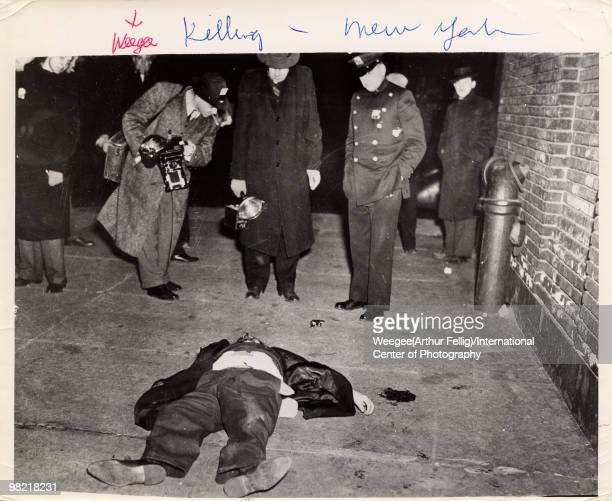 The noted photographer Arthur Fellig aka Weegee holds a Speed Graphic camera and smokes a cigar while looking down at a dead body lying on the...