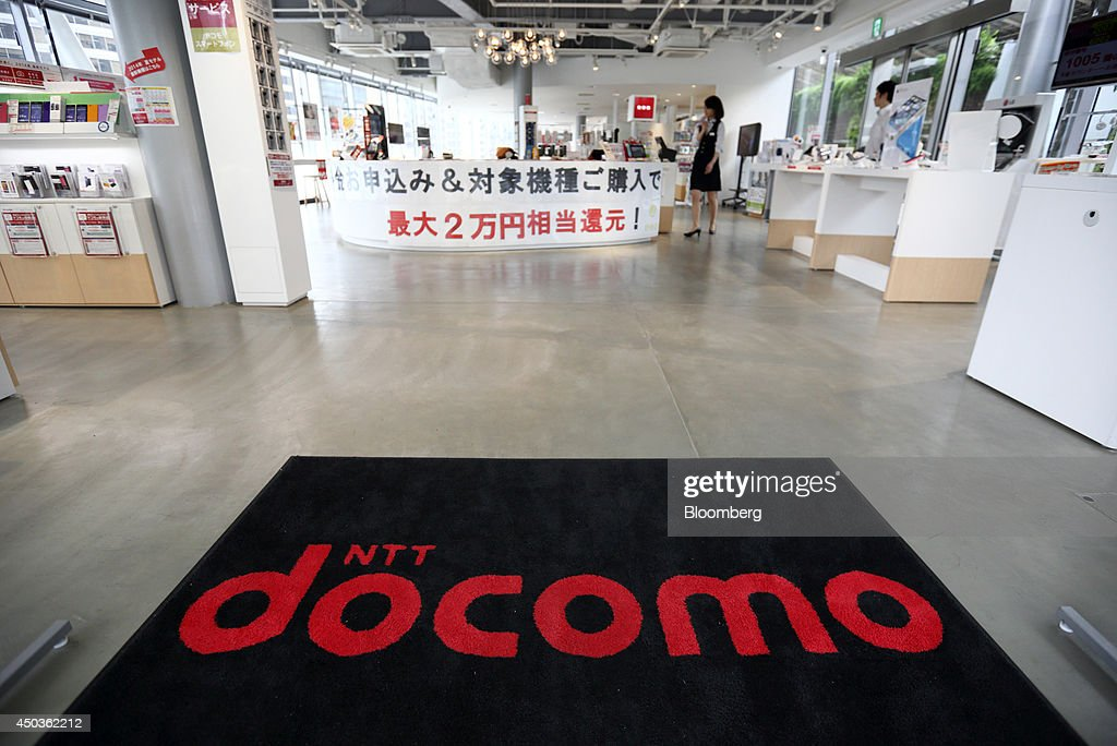 The NTT Docomo Inc. logo is displayed on a floor-mat as an employee walks through the company's store in Tokyo, Japan, on Tuesday, June 10, 2014. NTT Docomo, Japan's largest wireless carrier by subscribers, began offering Apple Inc's iPad today. Photographer: Tomohiro Ohsumi/Bloomberg via Getty Images