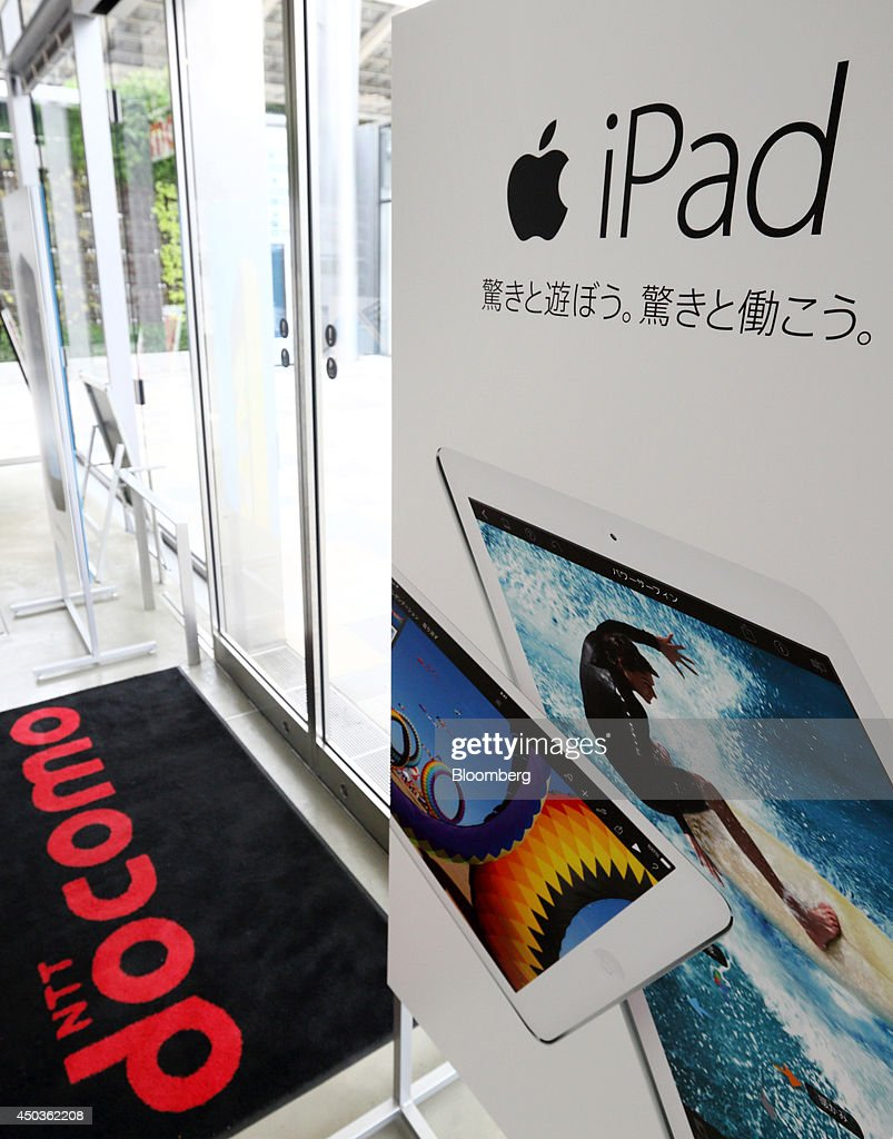 The NTT Docomo Inc. logo is displayed on a floor-mat next to an advertisement for the Apple Inc. iPad at an NTT Docomo store in Tokyo, Japan, on Tuesday, June 10, 2014. NTT Docomo, Japan's largest wireless carrier by subscribers, began offering Apple Inc's iPad today. Photographer: Tomohiro Ohsumi/Bloomberg via Getty Images