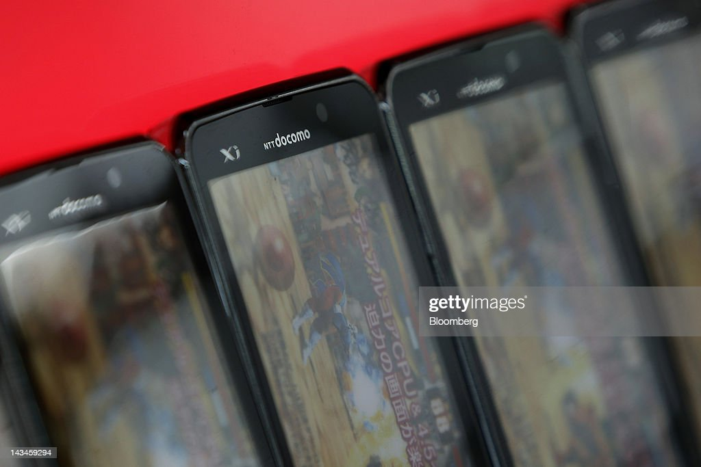 The NTT DoCoMo Inc. logo is seen on mock-up smartphones at the Labi Ofuna electronics store, operated by Yamada Denki Co., in Yokohama City, Kanagawa Prefecture, Japan, on Friday, April 27, 2012. Consumer prices excluding fresh food rose 0.2 percent from the year before, exceeding estimates, a government report showed earlier today. Photographer: Kiyoshi Ota/Bloomberg via Getty Images