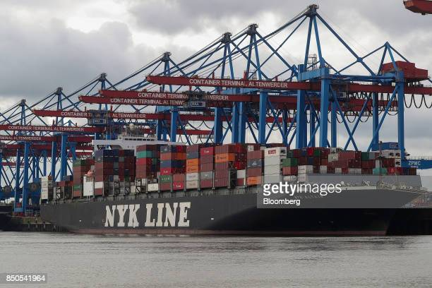 The NYK Altair container ship operated by Nippon Yusen KK stands loaded with cargo beside shiptoshore cranes at the Port of Hamburg in Hamburg...
