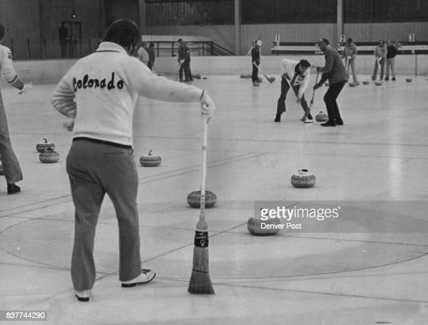 The object is to slide stones to center of target called 'House' At left skip Bunt Hubchik in foreground watches opponents Pete Peterman far left and...