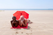 An older Caucasian man and an African woman relax together on a beach.
