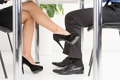 Woman's foot looking for man's foot under a business table.